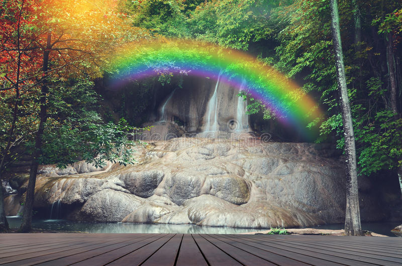 Waterfall with rainbow and wooden floor stock photography