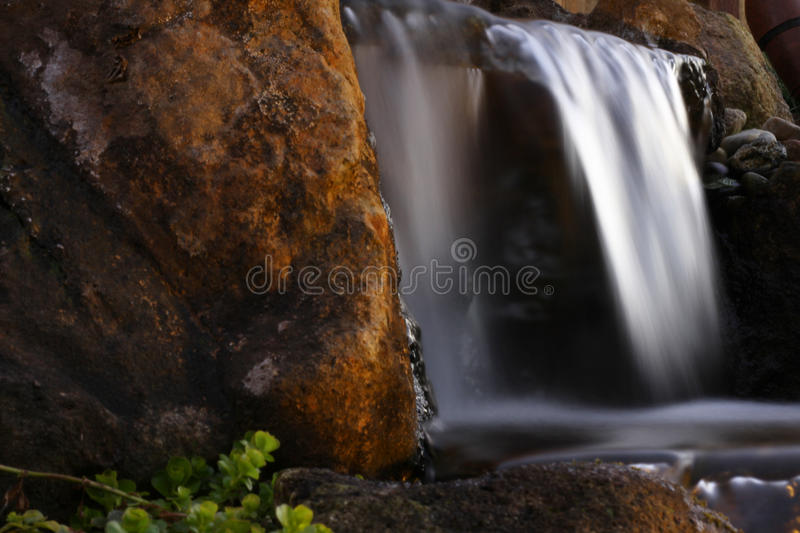 Misty waterfall cascading over cliffs. A blurred out misty waterfall cascading over a red brown rock cliff with some green plants in the foreground. Long royalty free stock images