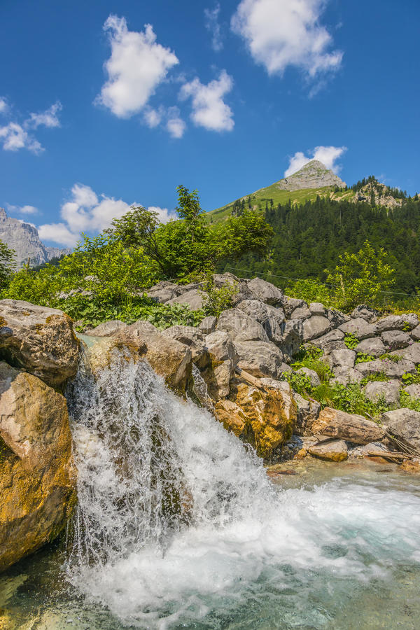 Waterfall and rocks in the Austrian Alps. Picture of a waterfall and rocks in the Austrian Alps with trees and mountains royalty free stock photography