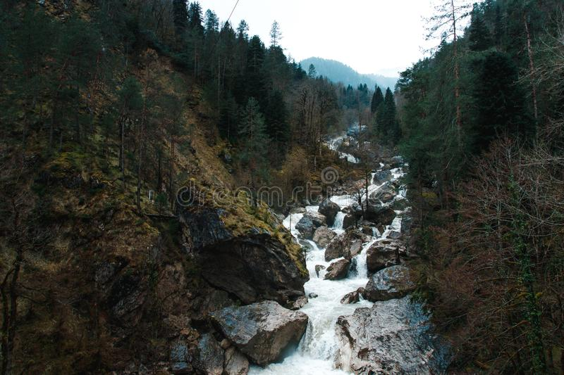 Forest and waterfall in rocky mountains. Small cliffy mountain spring waterfall in Abkhazia. Craggy ridge cliff with water bursts. Rocky mountains and waterfall royalty free stock image