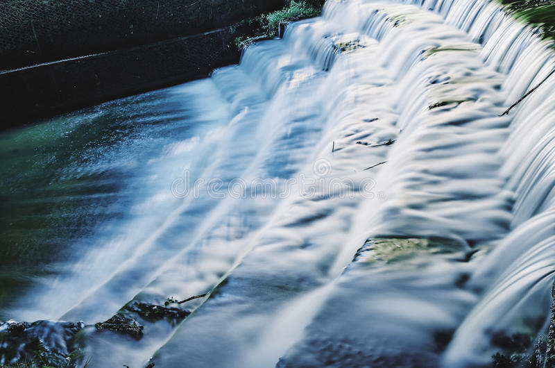 Waterfall in sequence of steps made by man on a long exposure ph stock photography
