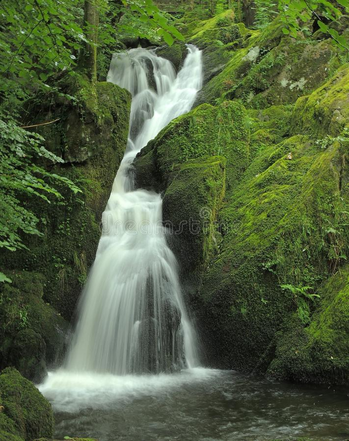 Waterfall. Smooth water stream through the hills and woods royalty free stock photography