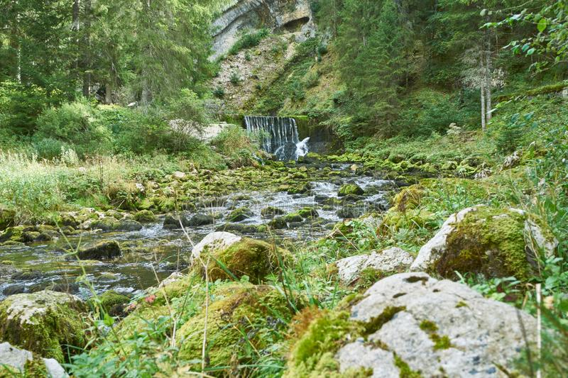 Waterfall at Source du Doubs Mouthe Franche Comté France with Green Plants. On A Sunny Day stock photo