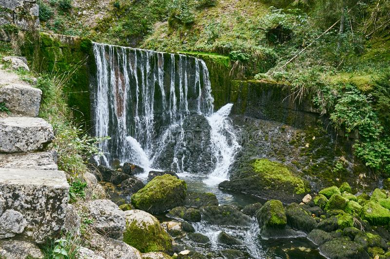 Waterfall at Source du Doubs Mouthe Franche Comté France with Green Plants. On A Sunny Day royalty free stock images