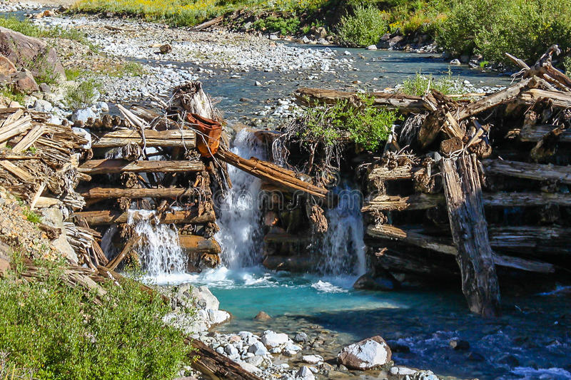 Waterfall Struture Falling Down. Old log structure giving way to the water flow in the mountain stream royalty free stock photography
