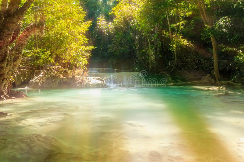 Waterfall with sun ray in tropical deep forest at Erawan National Park royalty free stock photography