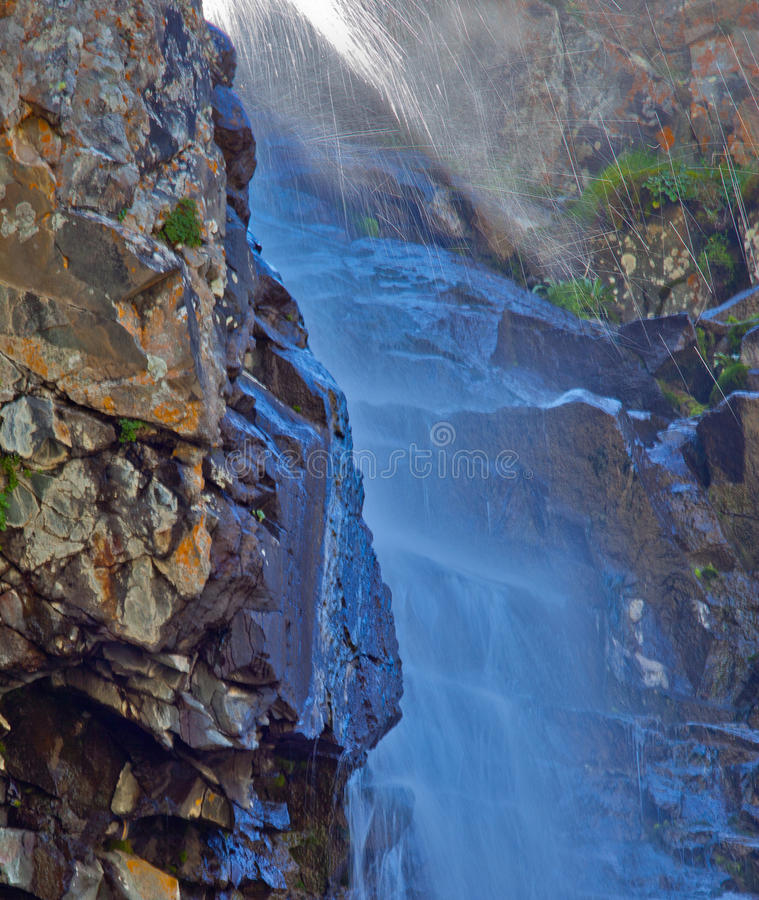 Waterfall with sunlight in the mountains, Ala-Archa, Kyrgyzstan. royalty free stock photography