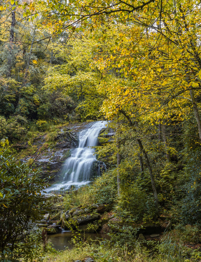 Waterfall surrounded by yellow fall color in forest royalty free stock photography