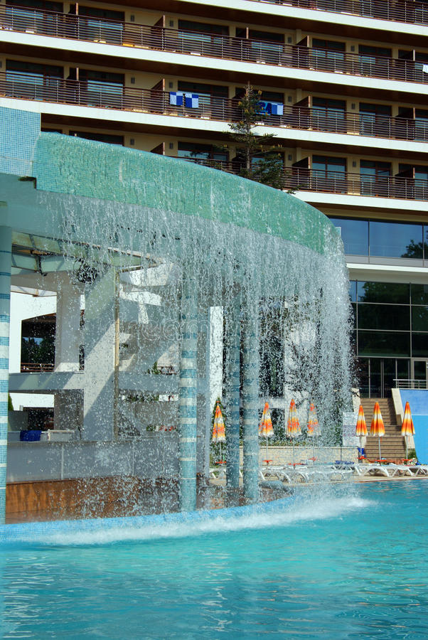 Waterfall and swimming pool in front of a hotel stock photo