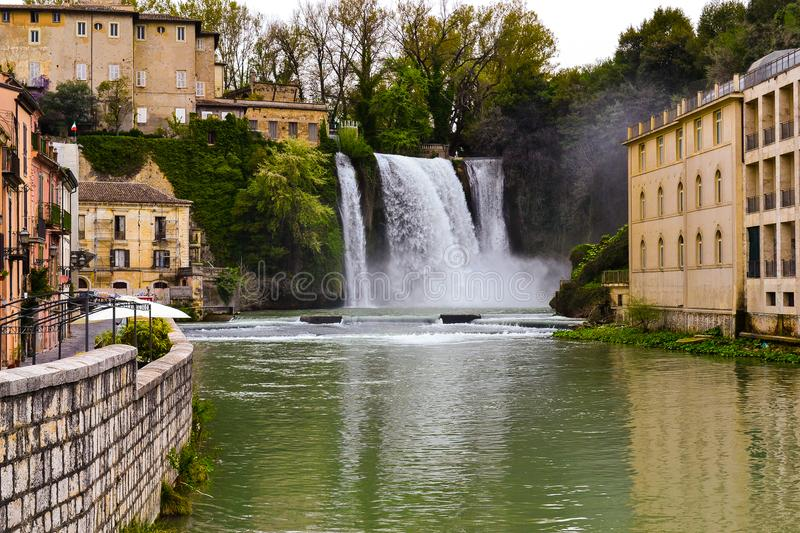 Waterfall in the town. Water splashes on the ground near buildings royalty free stock image