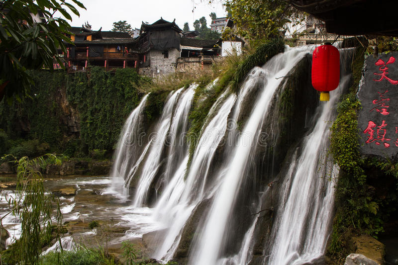 Waterfall under the ancient architecture at Furong Town of China royalty free stock photography
