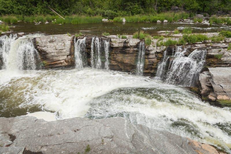 Waterfall under a bridge stock photos