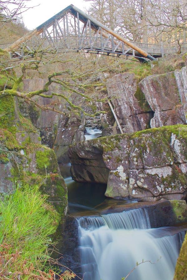 Waterfall Under Footpath Walking Bridge Running through the Woods royalty free stock image
