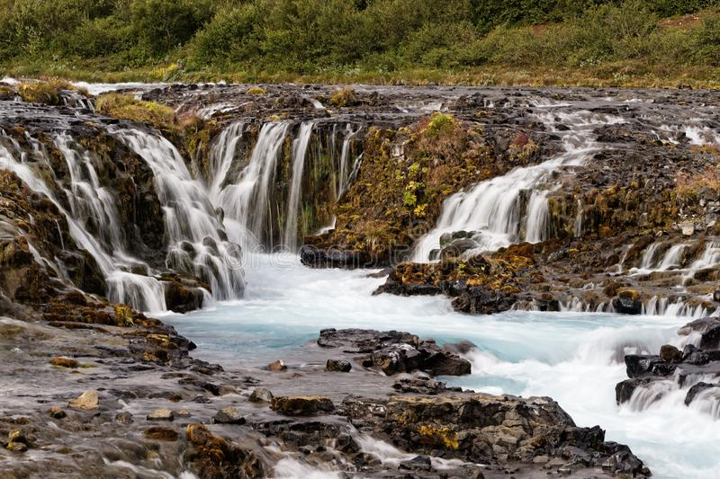 Waterfall in wild landscape in the evening light. Scenic view of a wild waterfall with many individual watercourses at a rock stage in the evening light, close stock images