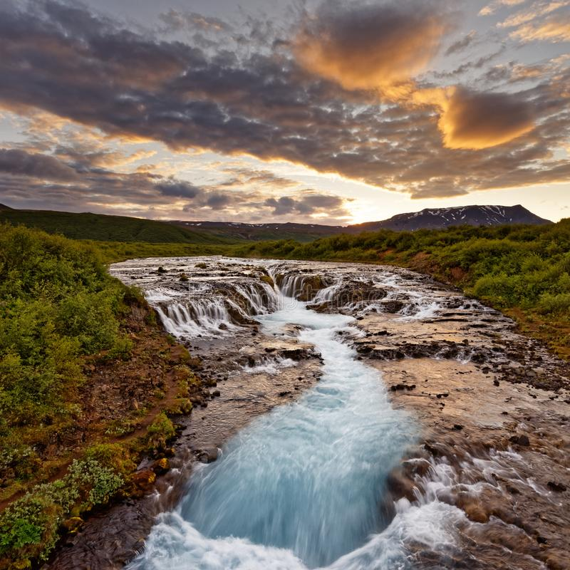 Waterfall in wild landscape after sunset stock photo