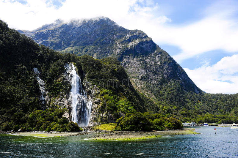 Waterfalls in Milford Sound New Zealand. With boats anchored stock photos