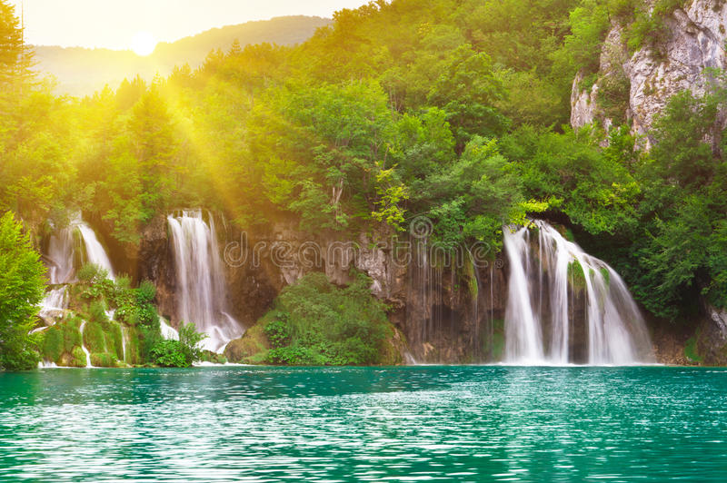Waterfalls in national park in sun rays royalty free stock images