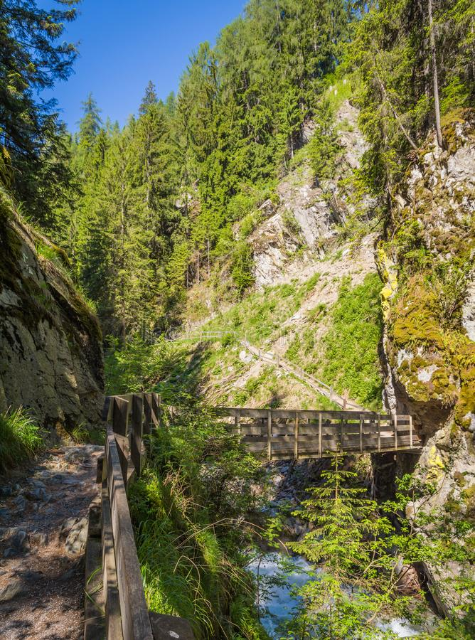 Waterfalls Stanghe Gilfenklamm localed near Racines, Bolzano in South Tyrol, Italy. Wooden bridges and runways lead through the stock photos