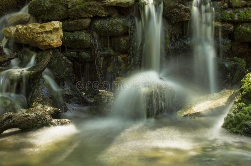 Waterfalls and streams of water among rocks and boulders royalty free stock images