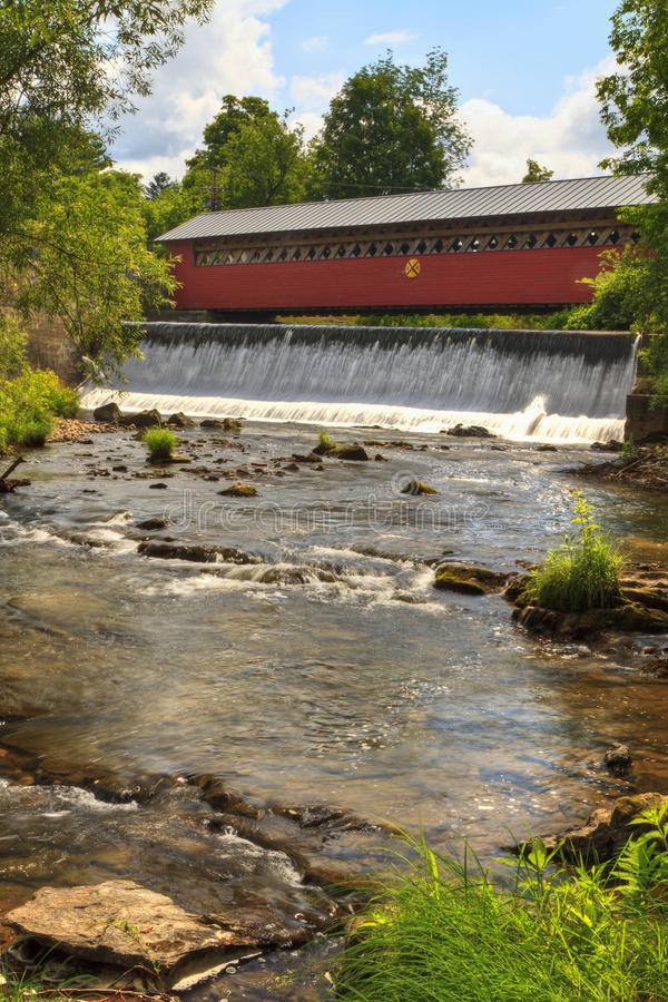 Bennington Covered Bridge and Waterfall. Waterfalls on the Walloomsac River below the historic Paper Mill Village Covered Bridge in Bennington, VT royalty free stock images