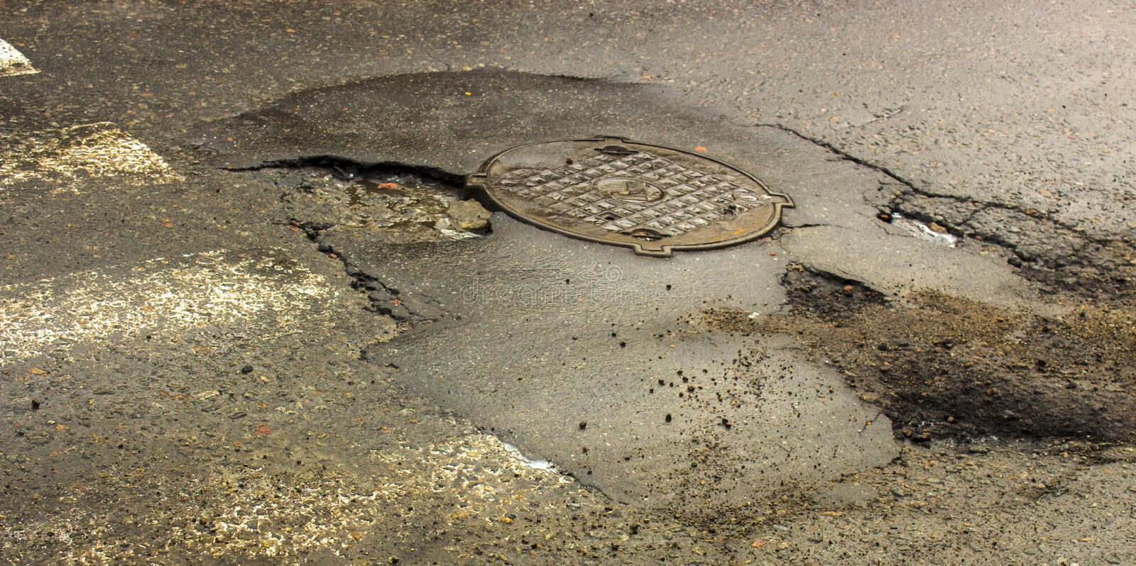 Waterfilled pothole on asphalted road royalty free stock photo