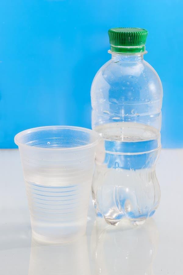 Waterfles en plastic kop met water stock foto's