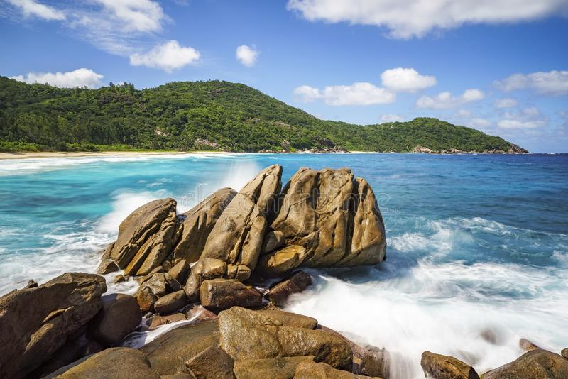 Waterfontein over granietrotsen, wild tropisch strand met palmen royalty-vrije stock foto's