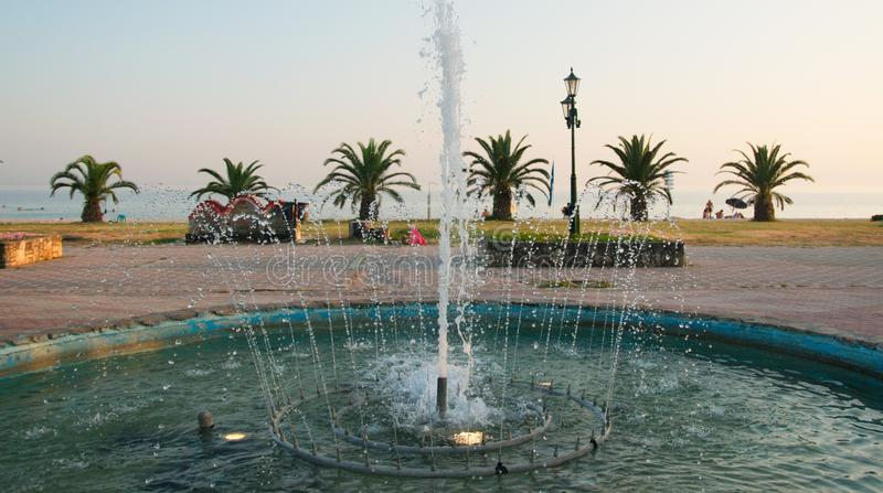 Waterfountain near palm trees. A picture of a waterfountain and palm trees in the background,near a summer beach,in a small town in Greece,New Flogita,in an area royalty free stock images