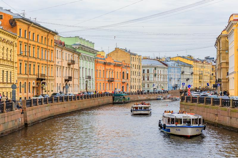 Waterfront buildings on the banks of river Neva and tourist boats on the water in Saint Petersburg. Beautiful waterfront buildings on the banks of the river Neva royalty free stock image