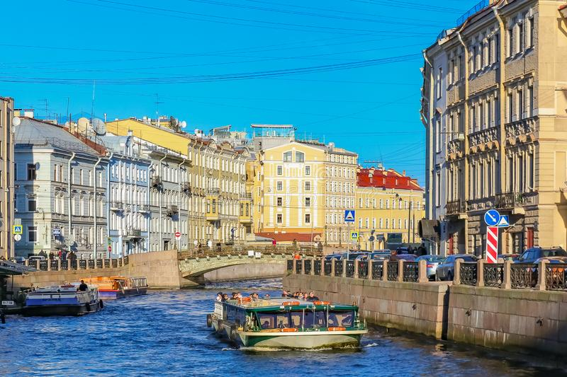 Waterfront buildings on the banks of river Neva and tourist boats on the water in Saint Petersburg. Saint Petersburg, Russia - October 04, 2015: Beautiful stock photography