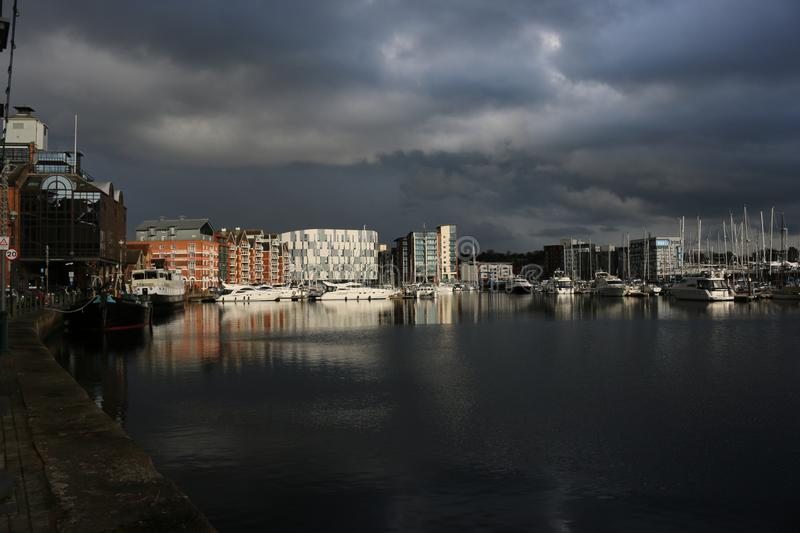 Ipswich waterfront marina with storm clouds. Waterfront marina and surrounding buildings in Ipswich, Suffolk, United Kingdom with very dark storm clouds and stock photos