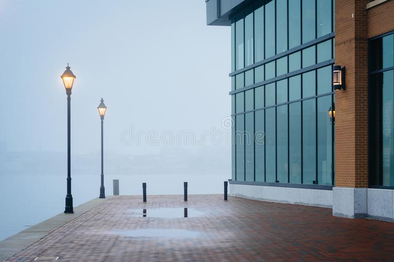 The Waterfront Promenade in fog and a modern building in Fells Point, Baltimore, Maryland royalty free stock photo