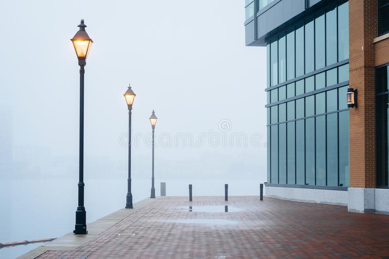 The Waterfront Promenade in fog and a modern building in Fells Point, Baltimore, Maryland royalty free stock photography