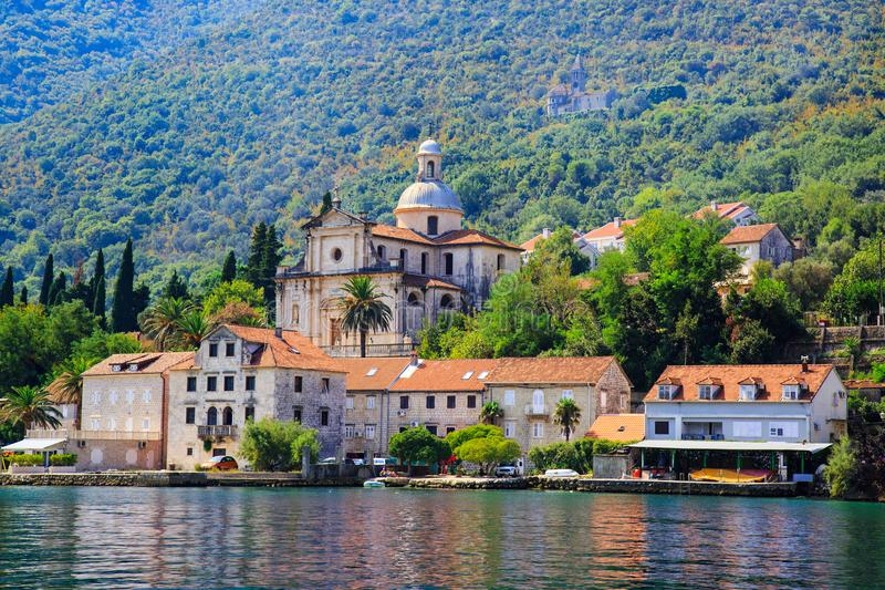 Waterfront of small town Prcanj along Bay of Kotor, Montenegro. View of Birth of Our Lady Church, coastal villas, gardens and moun royalty free stock photo
