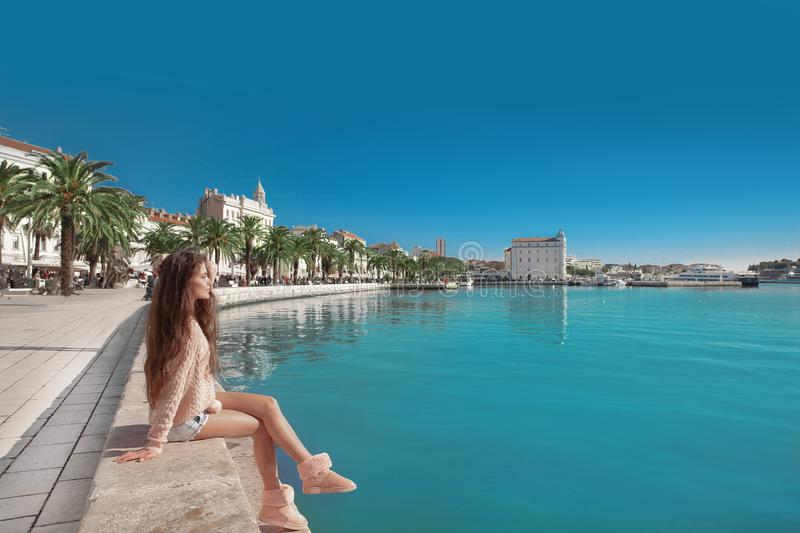 Waterfront of Split, Croatia. Young female traveler with pink ba royalty free stock photography