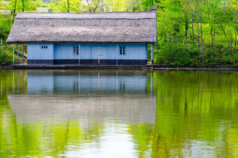 Waterfront wood house with thatched roof. Painted in blue stock image