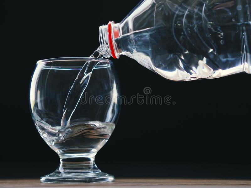 Waterglas en waterfles met water het vullen stock fotografie
