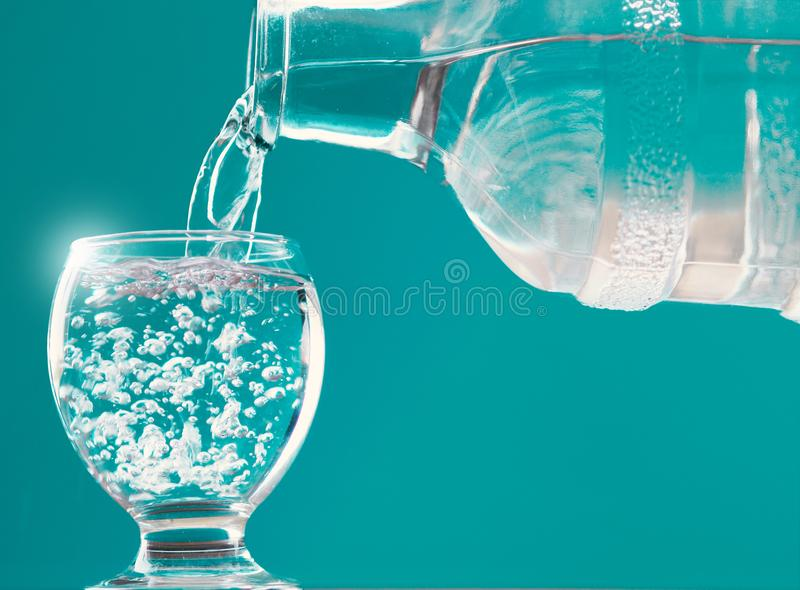 Waterglas en waterfles met water het vullen stock foto