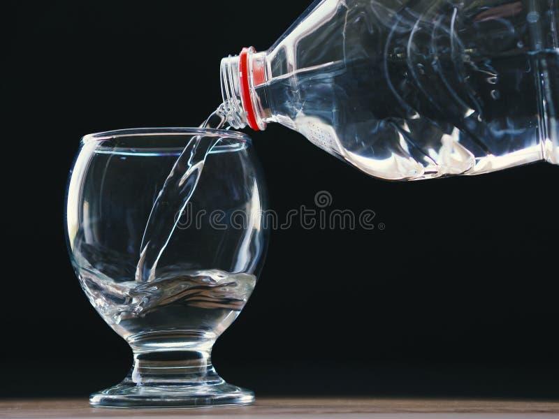 Waterglas en waterfles met water het vullen en zwarte achtergrond stock fotografie