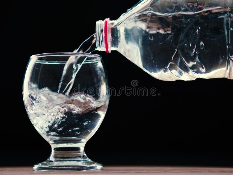Waterglas en waterfles met water het vullen en zwarte achtergrond stock afbeelding