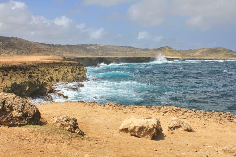 Watergolven die op de klippen van het eiland van Aruba verpletteren royalty-vrije stock fotografie