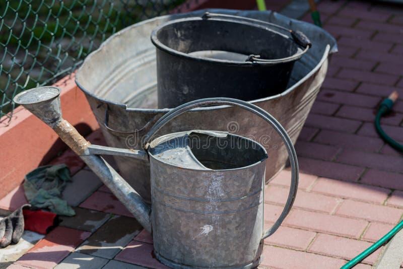 Watering buckets in the garden. Gardening concept image with metal bucket for water. Watering buckets in the garden. Gardening concept image with metal bucket stock photography