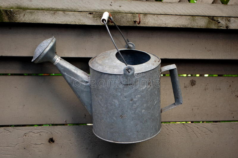 Watering Can. A garden watering can hangs on a rustic fence stock image