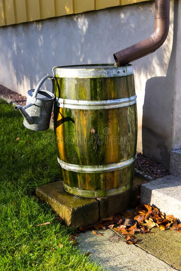 Watering can on barrel. A barrel of rain water next to a house stock photography