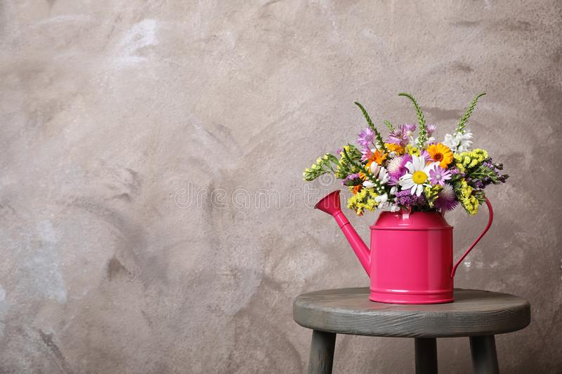 Watering can with beautiful wild flowers on table. Against grey background stock images