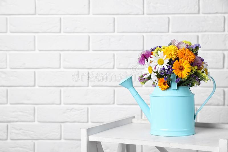 Watering can with beautiful wild flowers on table. Near brick wall stock image
