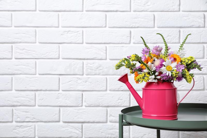 Watering can with beautiful wild flowers. On table near brick wall stock photo