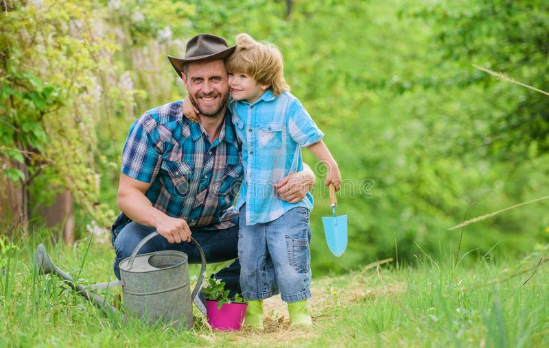 Watering can, pot and hoe. Garden equipment. father and son in cowboy hat on ranch. Eco farm. happy earth day. Family. Tree nursering. small boy child help stock image