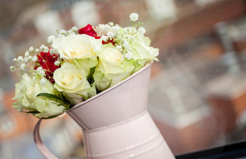 Watering can with roses bouquet stock image