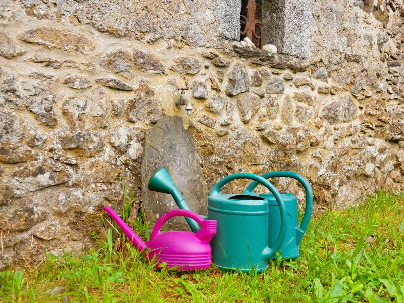 Watering cans for plants in the garden under a water tap near the stone wall of a village house.s stock photo